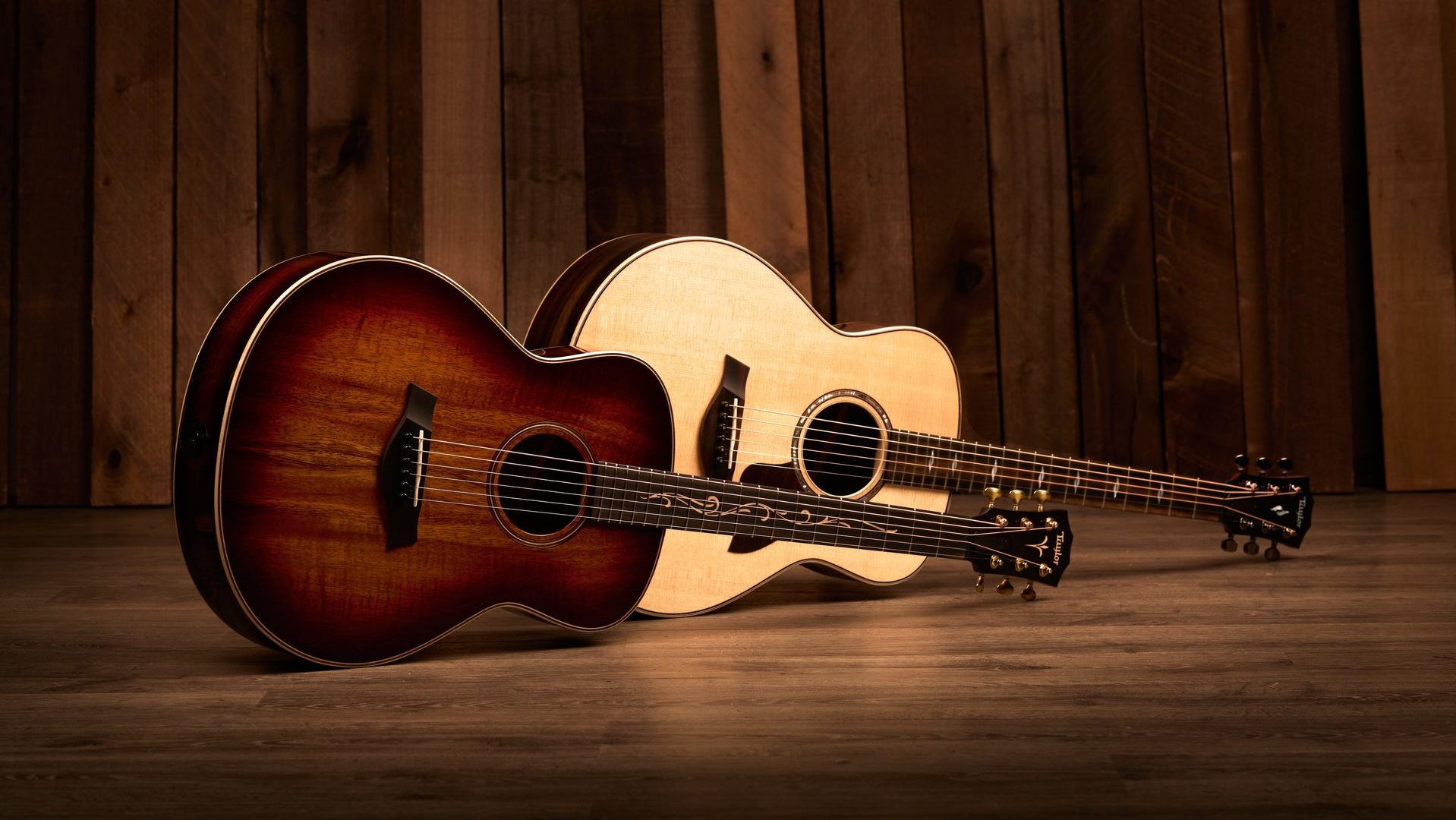 two Taylor GT acoustic guitars photographed horizontally with wood background