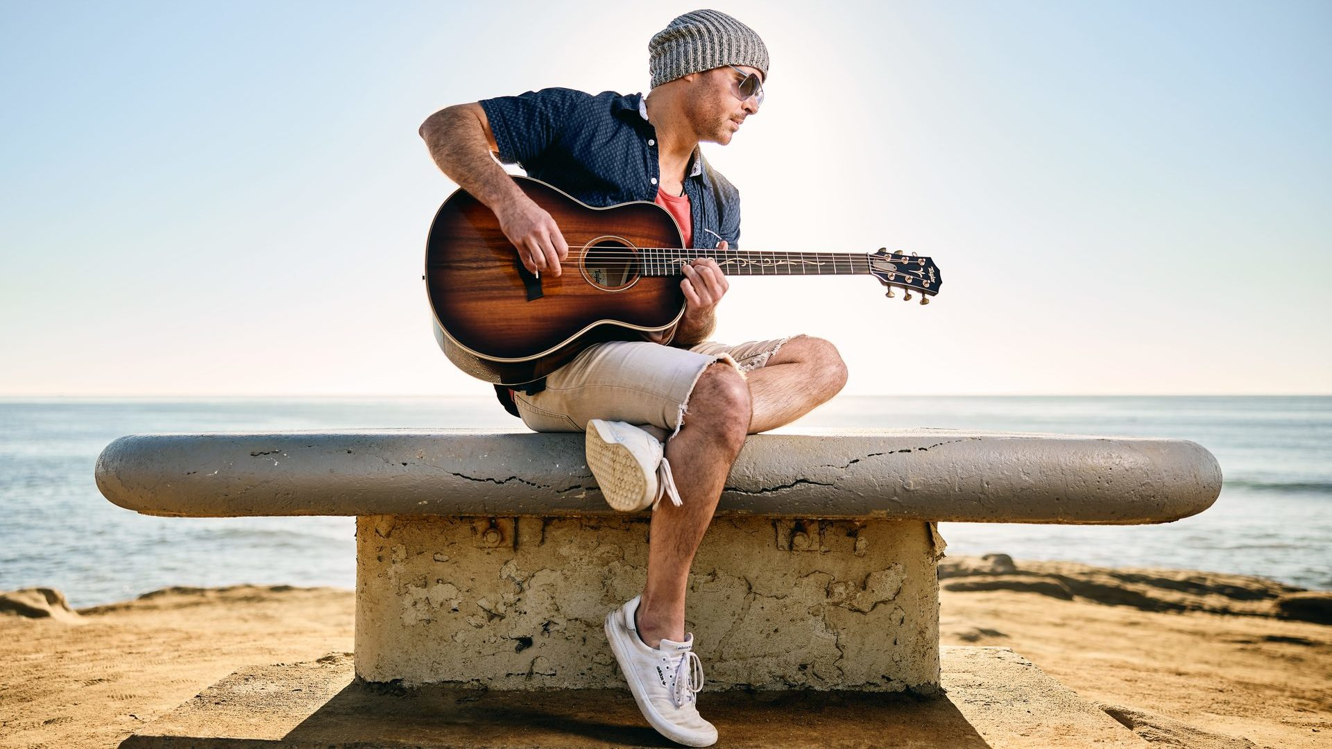 man playing Taylor GT K21e guitar on cement pedestal at the beach