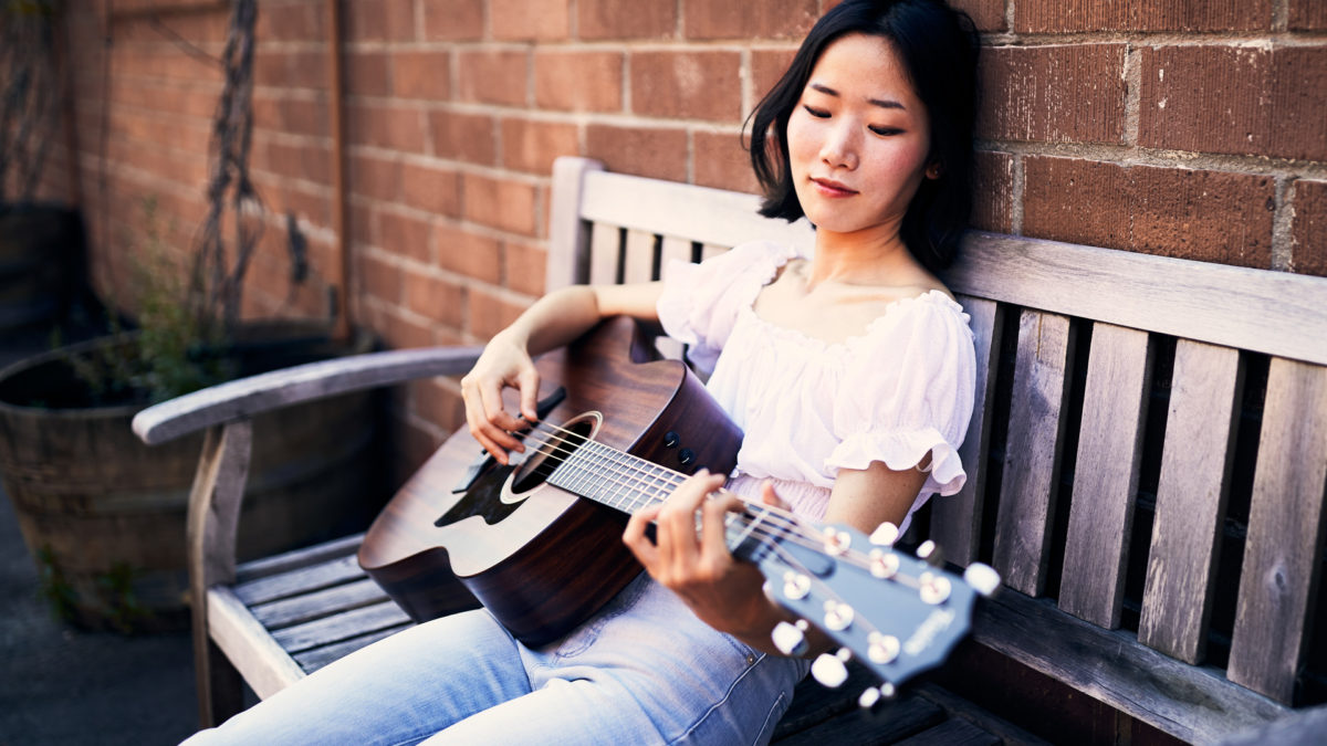 woman playing Taylor AD27 acoustic guitar on bench