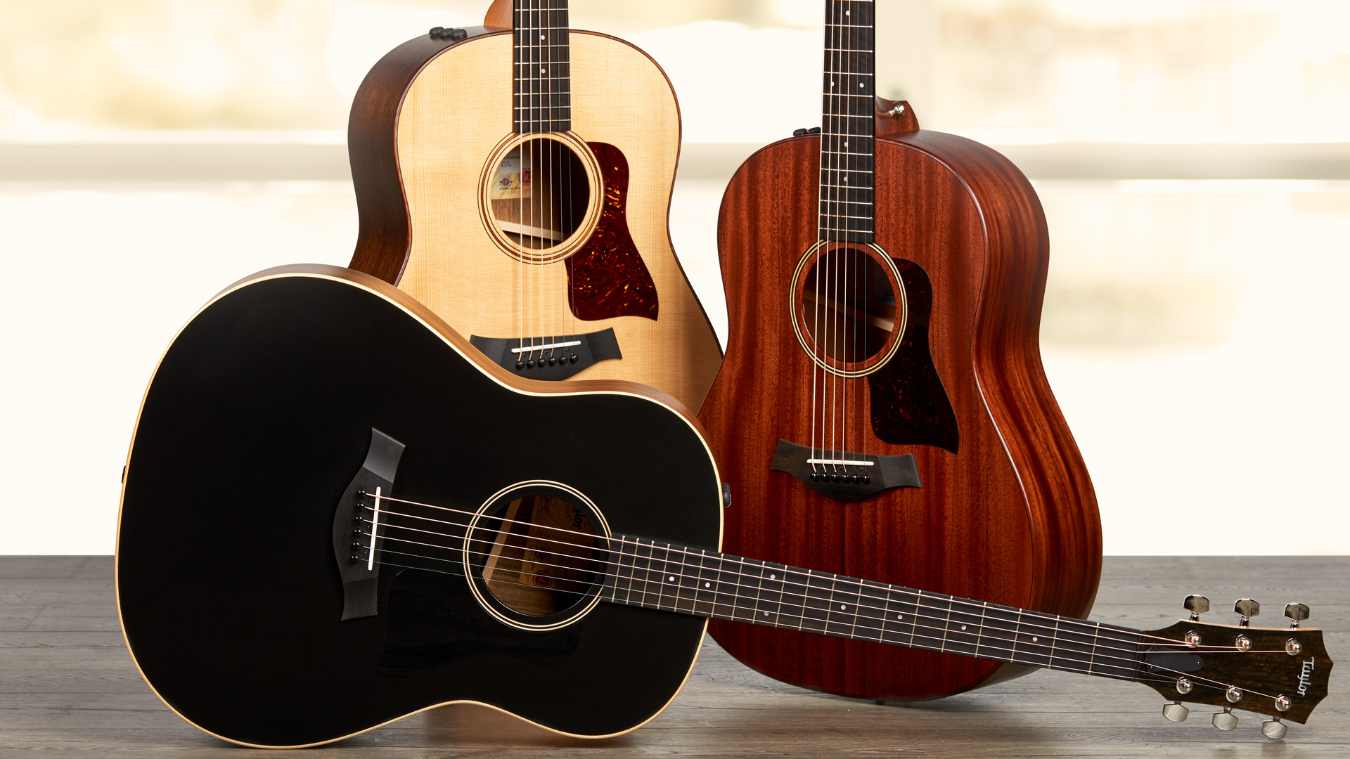 three taylor acoustic guitars in a row