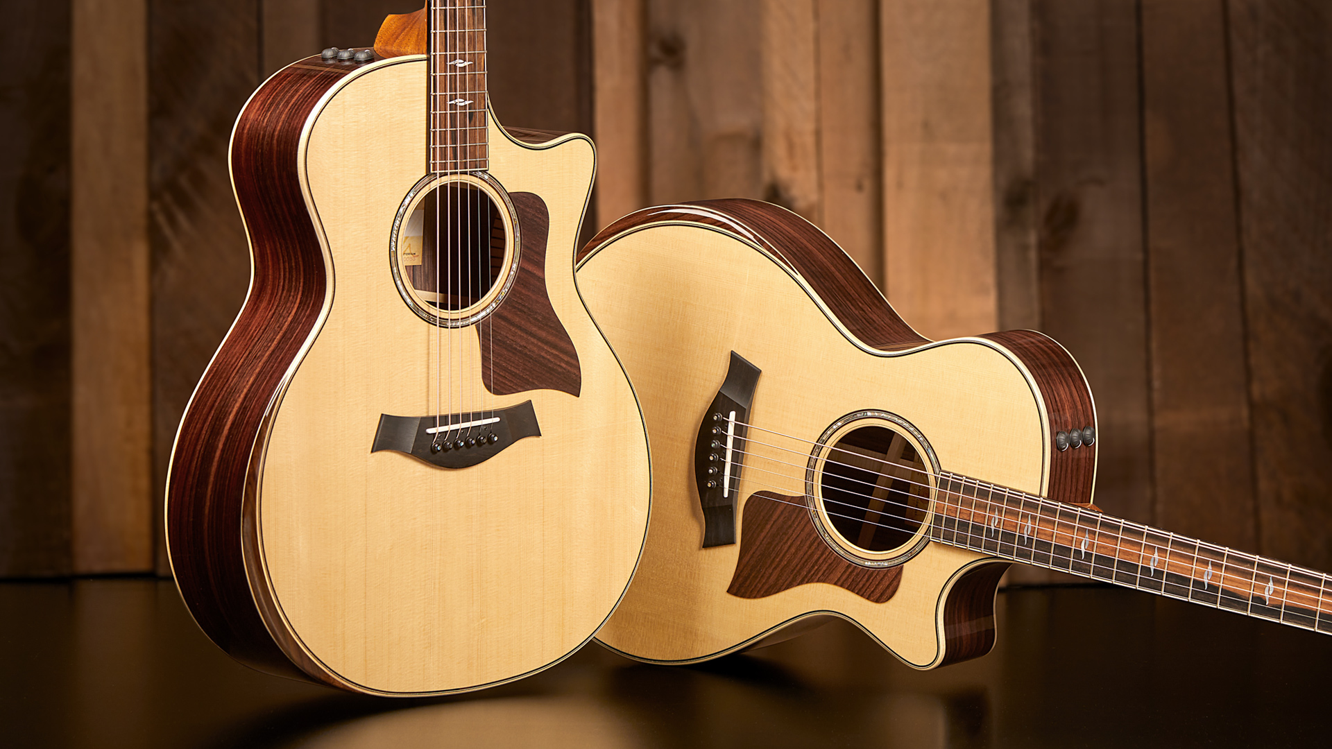 two taylor acoustic guitars, one standing and one leaning, facing front to display body shapes