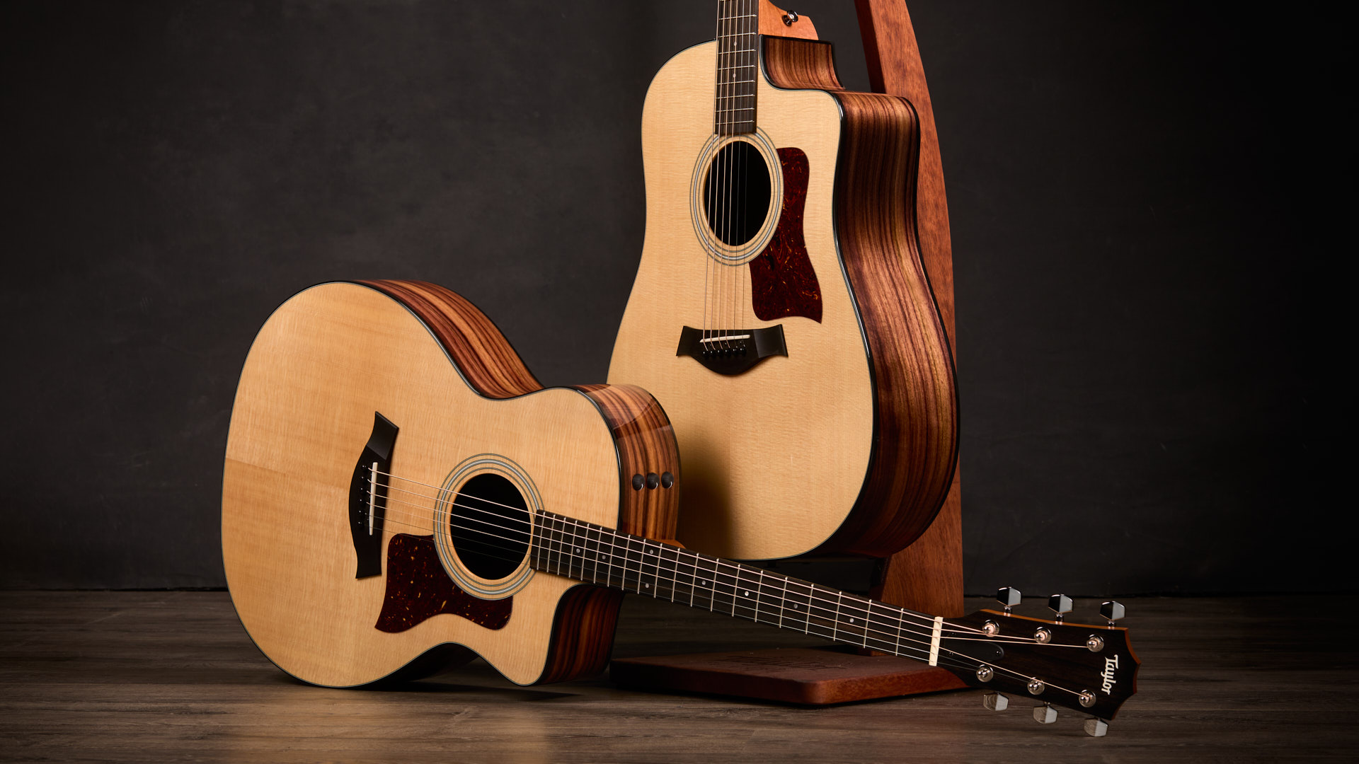 two Taylor acoustic 200 Series Plus guitars, one laying on its side in front and the other handing from a stand behind