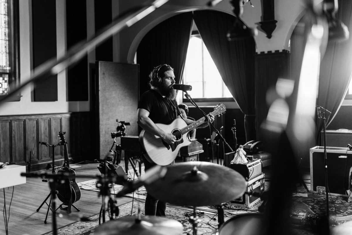 Manchester Orchestra singer and guitarist Andy Hull prepares to play in black and white photo