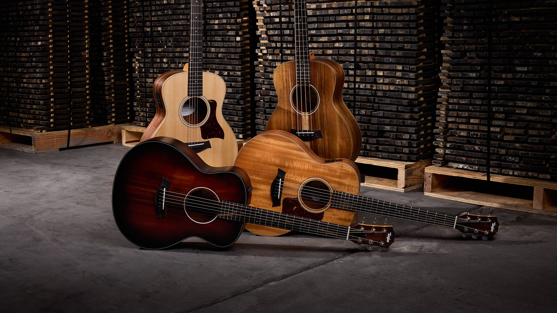 Four Taylor GS Mini acoustic guitars in a group with two standing vertically and two laying horizontally