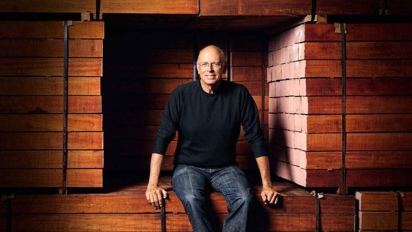 Bob Taylor seated on stack of mahogany wood